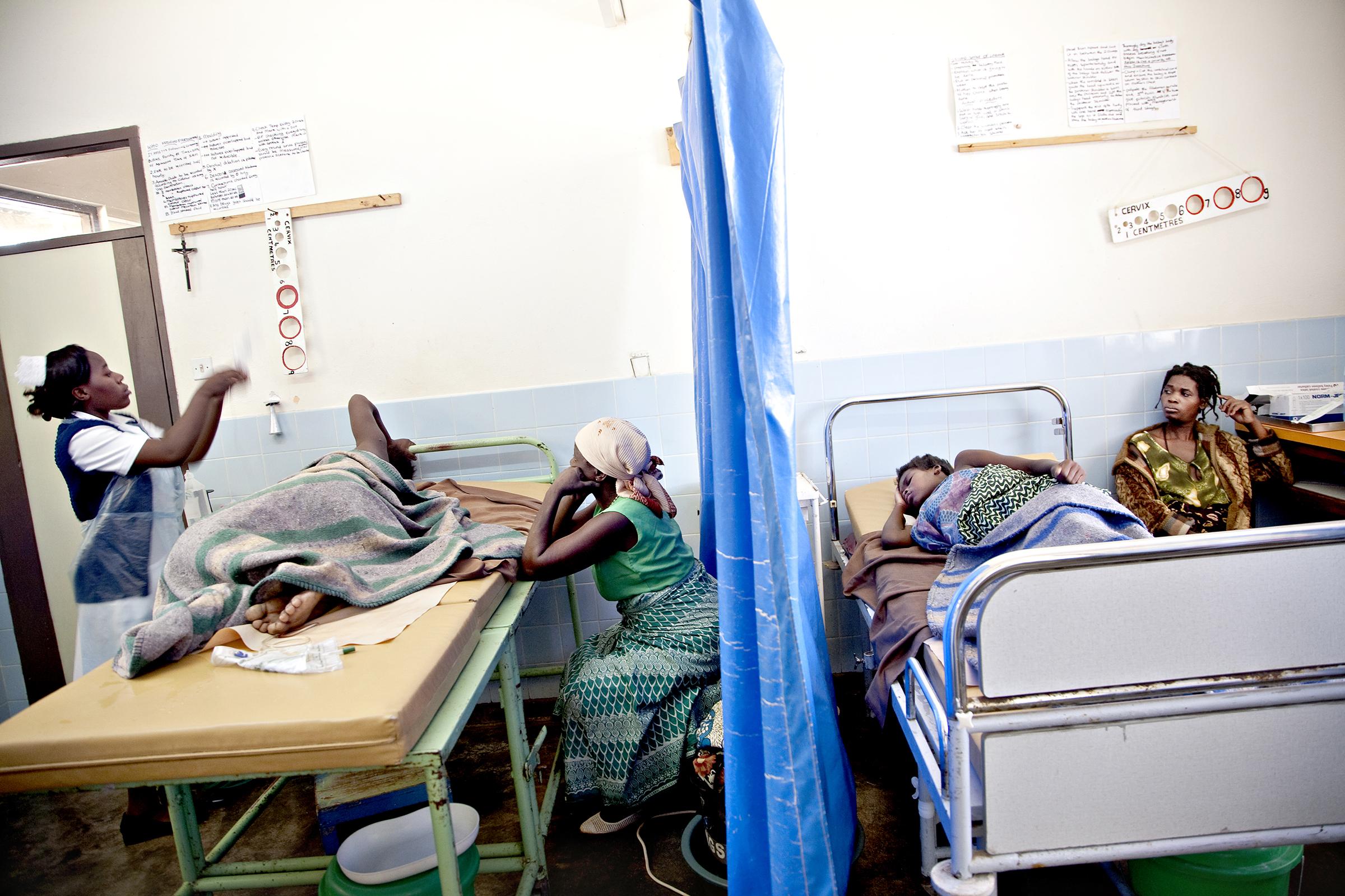 St. Joseph's Hospital, Chiradzulu, Malawi, 2010: På hver sin side av et blått plastikkforheng ligger Chrissy Andrew (34) og Modester Mosamba (16) og føder. Andrew har fire barn fra før, men dette svangerskapet ble annerledes. På kontroll fikk hun vite at hun er hivpositiv.
