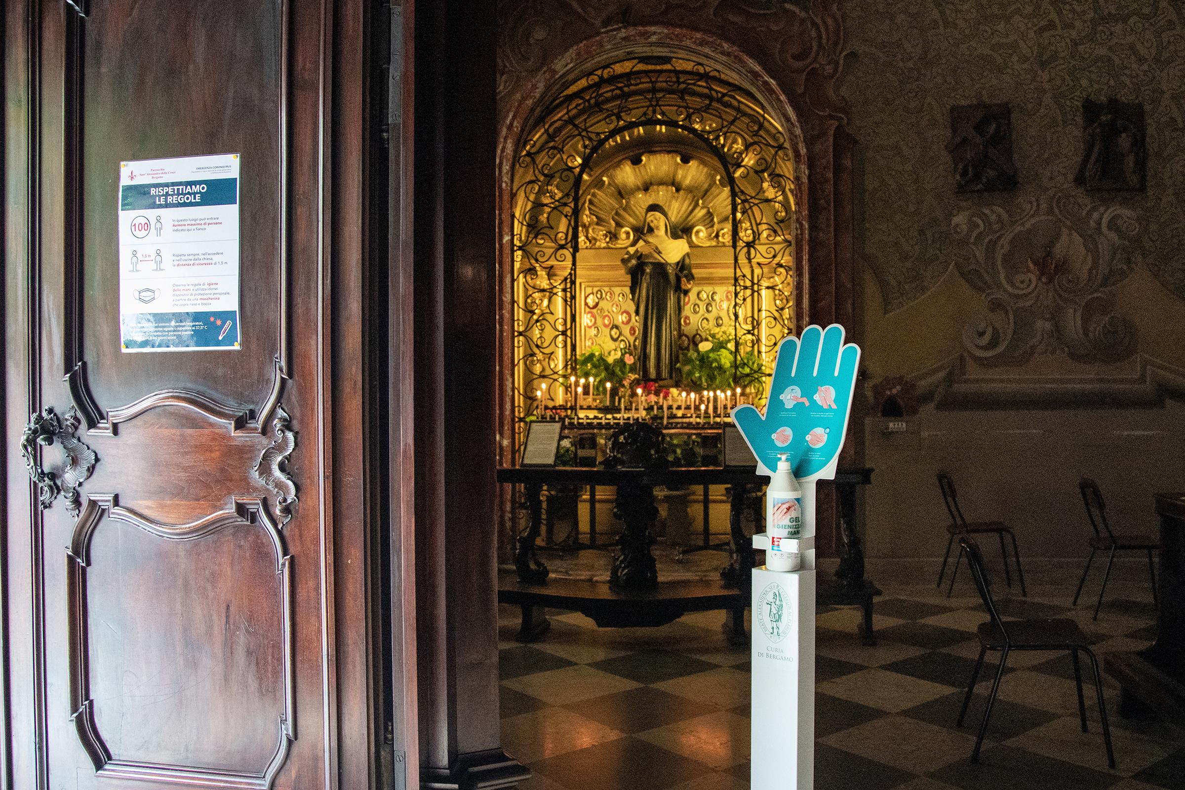 I kirken i Bergamo møtes vi av en hånd. Det er ikke noe hellig over den. Men som vi har lært dette året, det kan være livsviktig å følge dens instruksjoner.  Man må sprite hendene før man går inn.