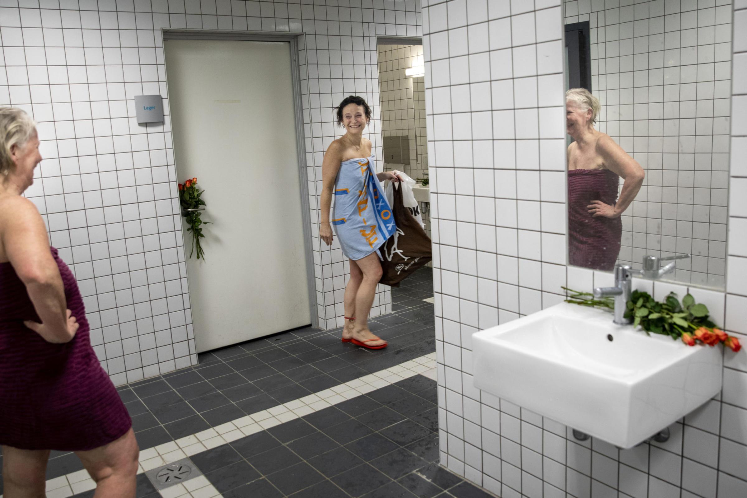 Cathrine Bye har svømt på Tøyenbadet i over 30 år. På badets siste åpningsdag har hun med roser som hun legger rundt omkring i damegarderoben.